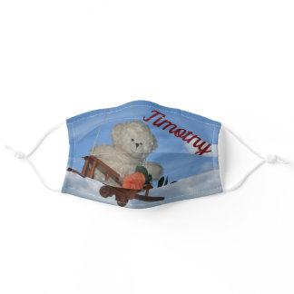 A teddybear flies with an airplane in a blue sky adult cloth face mask